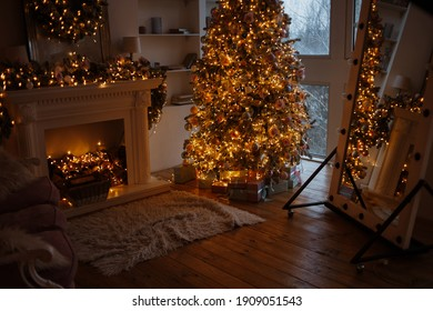 Luxury living room interior decorated with chic Christmas tree. warm cozy evening. Xmas tree decorated lights gifts, deer, candles, lanterns, garland lighting, floor mirror, fireplace.