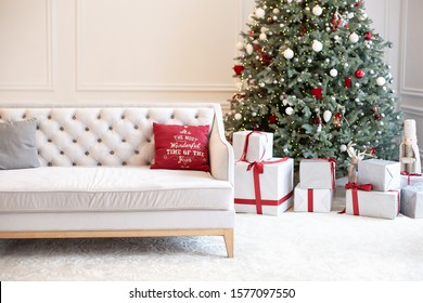 Luxury living room interior with sofa decorated chic Christmas tree, gifts and pillows. Classic interior in red shades. Christmas at home. beige sofa on background of Christmas tree.  New Year decor