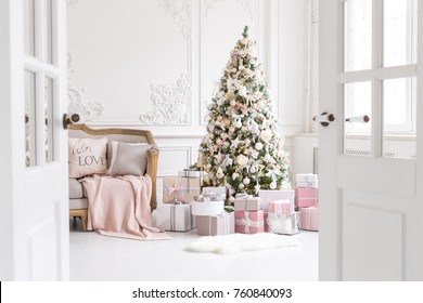 Luxury living room interior with sofa decorated chic Christmas tree, gifts, plaid and pillows.