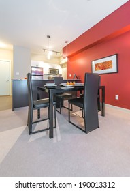 Luxury living suite : dining room with the nicely served table and red wall and the kitchen at the back . Interior design. Vertical.