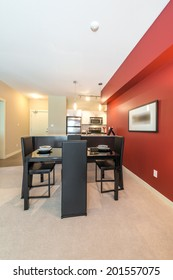 Luxury living suite with red walls: nicely decorated and served with pasta and fruits dining table and the kitchen at the back. Interior design.