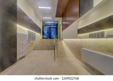 Luxury lobby interior. Flight stairway with stainless handrails and panoramic windows. There is illuminated mirror on wall. inscription above door Exit. Moscow 2018