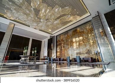Luxury lobby interior.With crystal lamp,bing hall, marble floor, french sash,mosaic tile,comfortable sofa, reception desk and long Escalators.