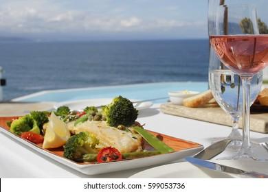 Un déjeuner de luxe avec un filet de poisson sur les légumes et un vin de rose avec vue sur l'océan