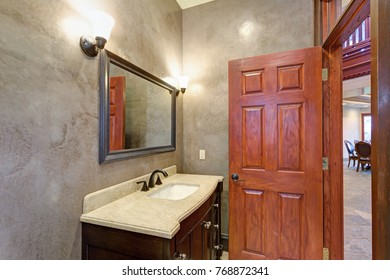 Luxury Mansion interior features New bathroom with grey stucco walls, rich brown vanity cabinet topped with white granite countertop accented with black faucet.