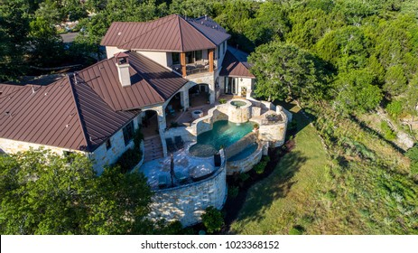 Luxury mansion on large lot of land with Texas hill country landscape and surrounding green surroundings of the ranch country home with infinity pool and wealthy real estate living side view of home