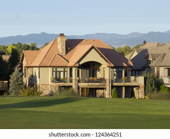Luxury mansion that backs onto a golf course in Denver, Colorado, with Rocky Mountains in the background.