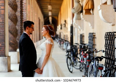 Luxury married wedding couple, bride and groom posing in old city near bicyclets