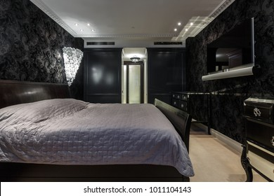 luxury master bedroom in dark colours with black wallpaper and  carpet flooring and stylish furniture and light
