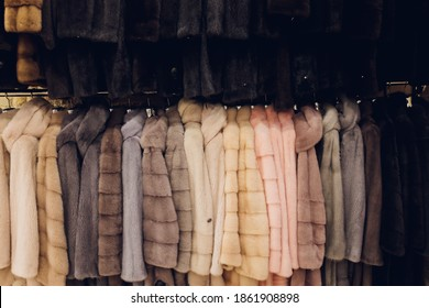Luxury mink coats. Grey, brown, pearl color fur coats on showcase of market. Best gift for women is mink coat. Outerwear. Close up.