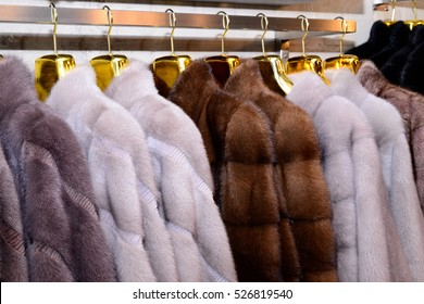 Luxury mink coats. Grey, brown, pearl color fur coats on showcase of market. Best gift for women is mink coat. Outerwear. Collection of 2017 year. New collection.
