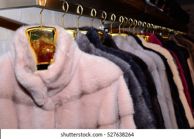 Luxury mink coats. Grey, brown, pearl, pink color fur coats on showcase of market. Best gift for women is mink coat. Outerwear.