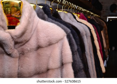 Luxury mink coats. Grey, brown, pearl, pink, black color fur coats on showcase of market. Best gift for women is mink coat. Outerwear.