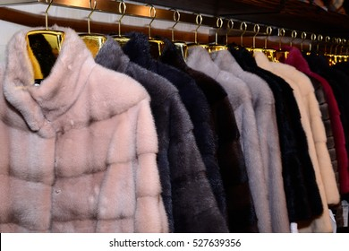Luxury mink coats. Grey, brown, pearl color fur coats on showcase of market. Best gift to women is mink coat. Outerwear. Close up.