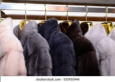Luxury mink coats. Pink, grey, dark grey, pearl color fur coats on showcase of market. Best gift for a woman. Outerwear. Close up.