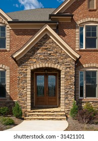 Luxury Model Home Exterior stone arch front entrance view
