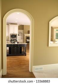 Luxury Model Home Kitchen through Arch door