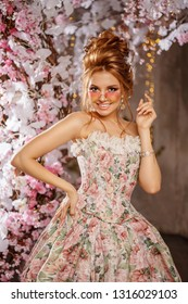 Luxury model in vintage style. Beautiful woman with a stunning hairstyle and make-up in a rococo dress. Girl at the Masquerade Spring Ball