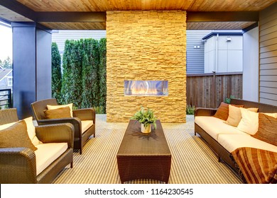 Luxury modern deck exterior with stone fireplace and wooden ceil