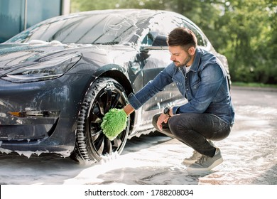 Luxury modern electric car in soap foam outdoors at car wash service. Side view of handsome young Caucasian man using green microfiber car wash mitt for cleaning rims outdoors.