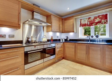 Luxury modern fitted kitchen with stainless steel appliances, granite work surfaces and two ovens