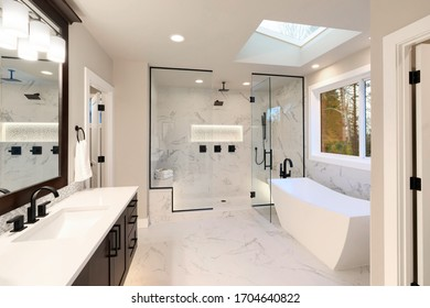 Luxury modern home bathroom interior with dark brown cabinets, white marble, walk in shower, free standing tub, two mirrors, flowers.