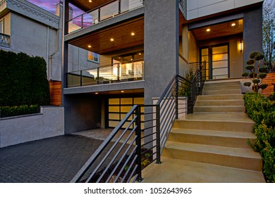Luxury modern home entrance with stairs and horizontal railings.