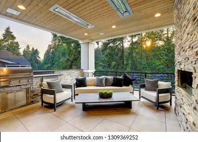 Luxury modern house exterior with covered patio boasting stone fireplace and cozy rattan furniture.