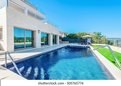 Luxury modern house with swimming pool with waterfall jet. House marble