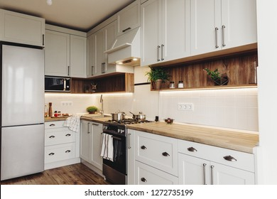 Luxury modern kitchen furniture in grey color and steel oven,fridge, sink, wooden tabletop, pots,. Gray cabinets in scandinavian style. Home renovation. Stylish kitchen interior design.