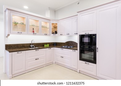 Luxury modern light beige kitchen, embedded microwave and electric oven, gas stove, minimalistic clean design
