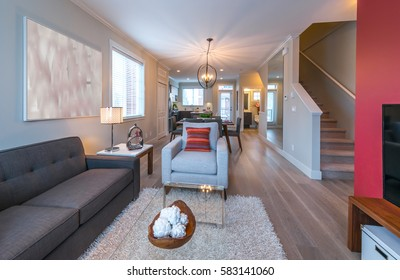 Luxury modern living suite, room with sofa and chairs and nicely decorated coffee table and the kitchen at the back.  Interior design.