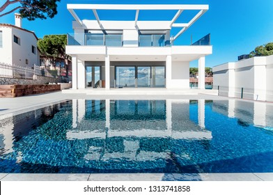 Luxury modern white house with large windows overlooking a Mediterian landscaped garden with palm trees and  blue swimming pool. High tech style villa. Vacation home or hotel. Modern loft design.