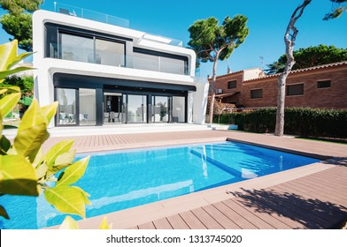Luxury modern white house with large windows overlooking a Mediterian landscaped garden with palm trees and  blue swimming pool. High tech style villa. Vacation home or hotel. Modern loft design.ees a