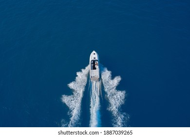 luxury motor boat. Aerial view of a boat in motion on blue water. Top view of a white boat sailing in the blue sea. Drone view of a boat sailing at high speed. - Shutterstock ID 1887039265