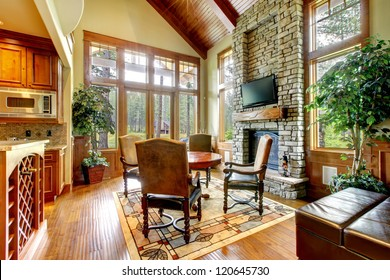Luxury mountain home dining and living room with stone fireplace.