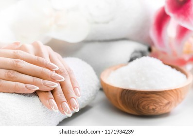 Luxury nails french manicure concept. Woman in cosmetics salon with towels, salt in olive bowl and flowers in background. Relaxing hands massage or spa treatment procedure.