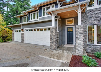 Luxury new construction home with high porch with stone columns, two garage spaces and concrete driveway.