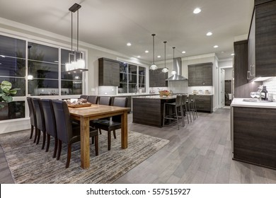 Luxury New construction home with open floor plan: dining and kitchen design. Rustic wood dining table matches with modern style leather chairs. Kitchen accented with dark cabinetry. Northwest, USA