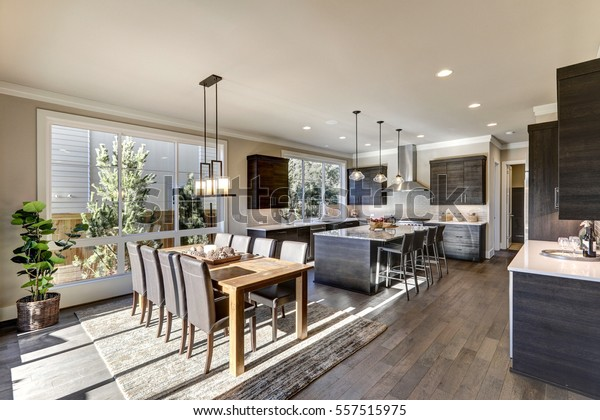 Luxury New construction home with open floor plan: dining and kitchen design. Rustic wood dining table matches with leather chairs. Kitchen accented with dark cabinetry. Northwest, USA