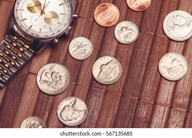 Luxury but not new watch with coins. Cost-is-no-object, time is money, poor income concept. Vintage tone image
