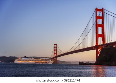 A luxury ocean liner passenger ship, leaving San Francisco Bay, sailing underneath the Golden Gate Bridge, photographed from Horseshoe bay, in Marin County, near Fort Baker.