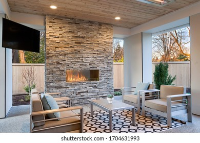 Luxury outdoor relaxing living room with large stone fireplace, TV, rug and beige sofa.