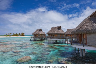 Luxury overwater bungalows on top of coral reef in tropical paradise