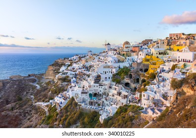 Luxury panoramic view over houses and villas in Oia village in the evening at sunset. Beautiful natural and architectural landscape at summer season. Santorini ( Thira ) island.Cyclades.Greece.Europe.