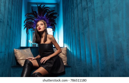 Luxury party and celebration concept - beautiful woman in black dress and in the Brazilian accessories in club with blue background