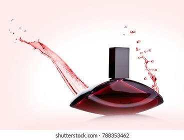 Luxury pink red liquid  perfume bottle with splashes on pink background