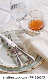 Luxury porcelain dishes, silverware lying across the dishes, crystal glassware and a glass of cognac on white vintage lace tablecloth
