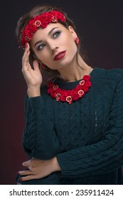 Luxury portrait of beautiful girl with red decorations in the form of small garnets