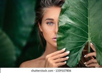 Luxury Portrait of a Beautiful  young woman with natural makeup holds a  big green leaf on a  blurred green background. Spa and wellness. Youth, teens and skin care concept. Close up